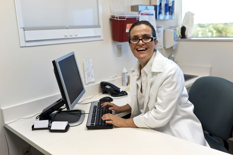 A smiling medical professor at her computer