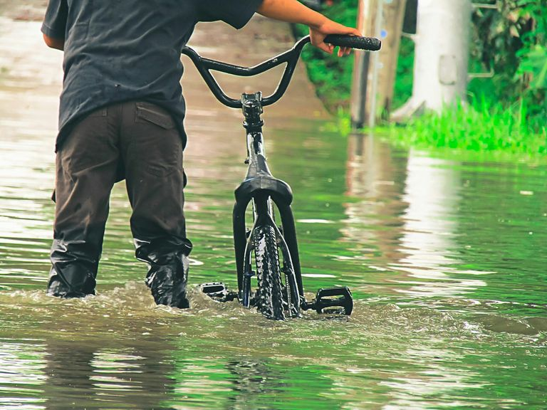Man With Bicycle Walking Through Flood Water