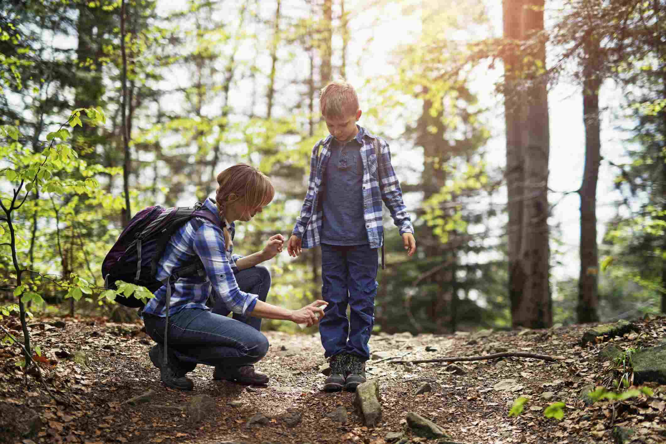 Mother applying bug repellent on son