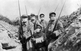 French troops wearing an early form of gas mask in the trenches during the 2nd Battle of Ypres.