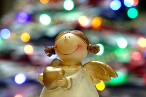 Angel statue holding a heart in front of a blurry Christmas tree with multicolored lights.
