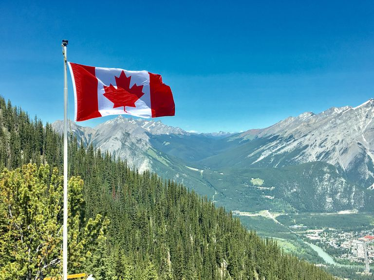 Canadian flag flying next to a mountain range.