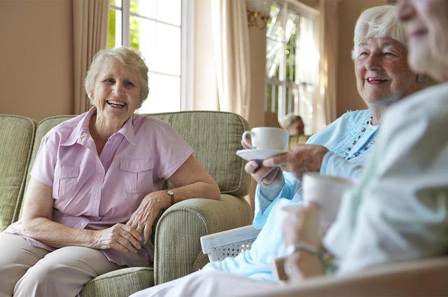 Elderly women, aged 75-85, talking and drinking tea together in a private retirement home