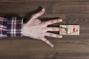 A man's finger trapped in a mousetrap, close-up of hand