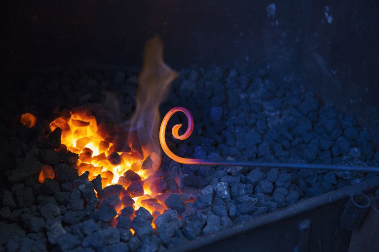 Close up of glowing metal rod with a scrolled end, held over hot coals in a blacksmiths workshop