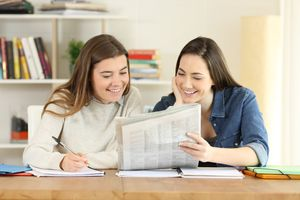 Students reading a newspaper and taking notes