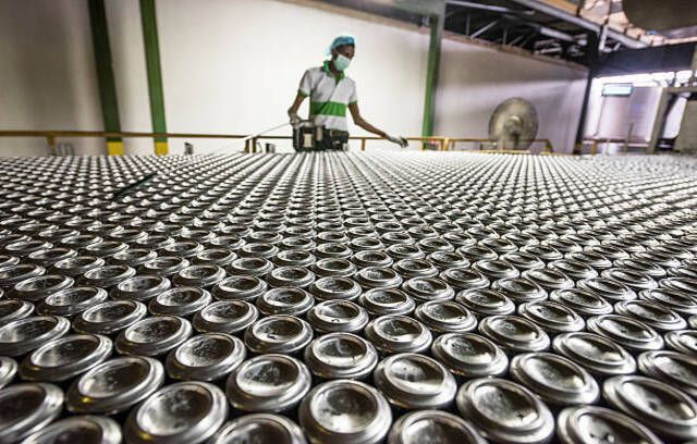Male factory worker wearing mask working on production line of aluminium drink cans being produced in processing plant
