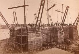 Photograph of a Brooklyn Bridge tower under construction.