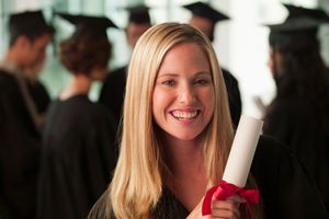 woman smiling and holding school diploma