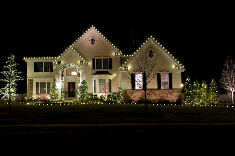 white lights along the eaves of three front gables of a white house a outdoor christmas decorations