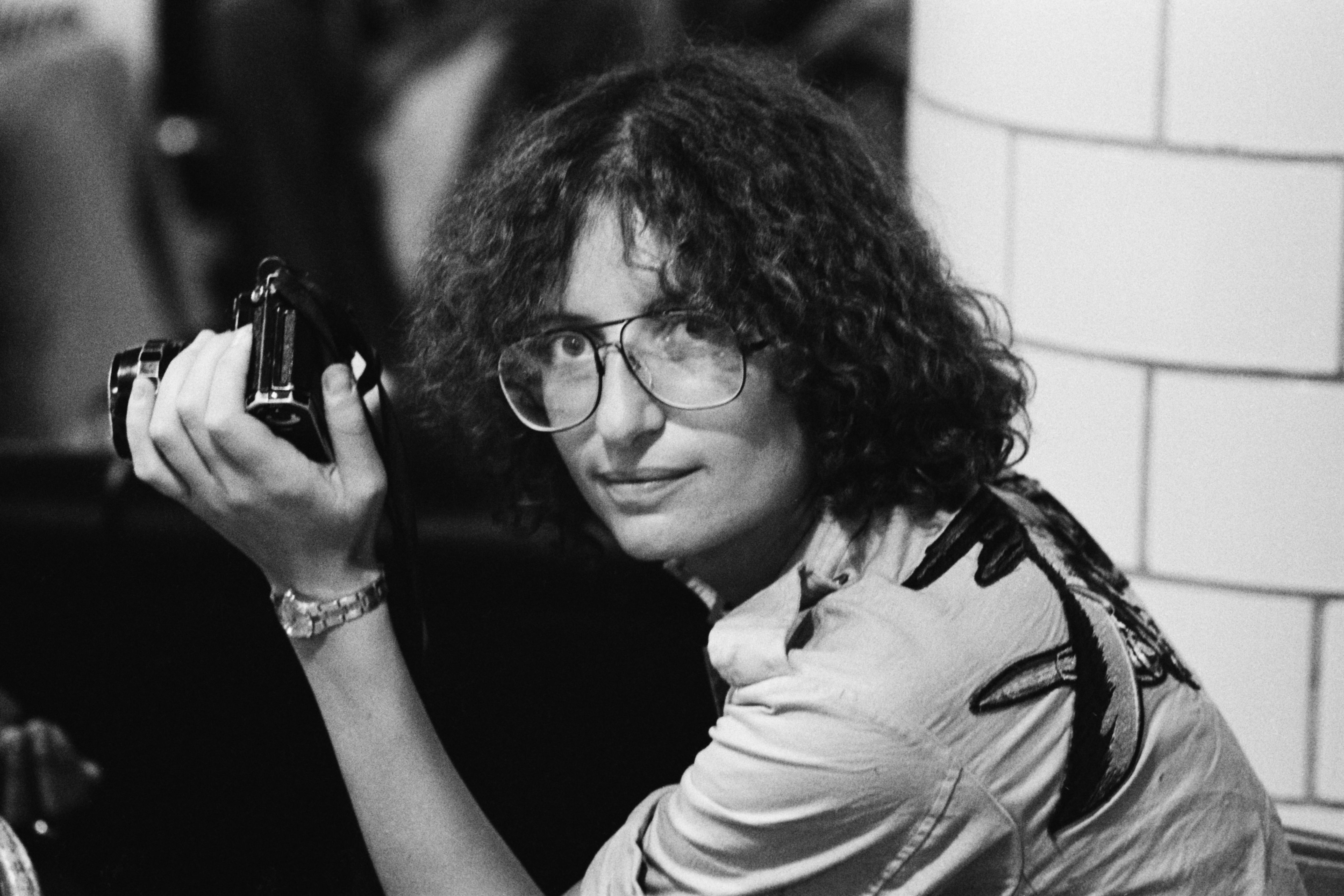 Annie Leibovitz with camera during the Rolling Stones Tour of the Americas, 1975