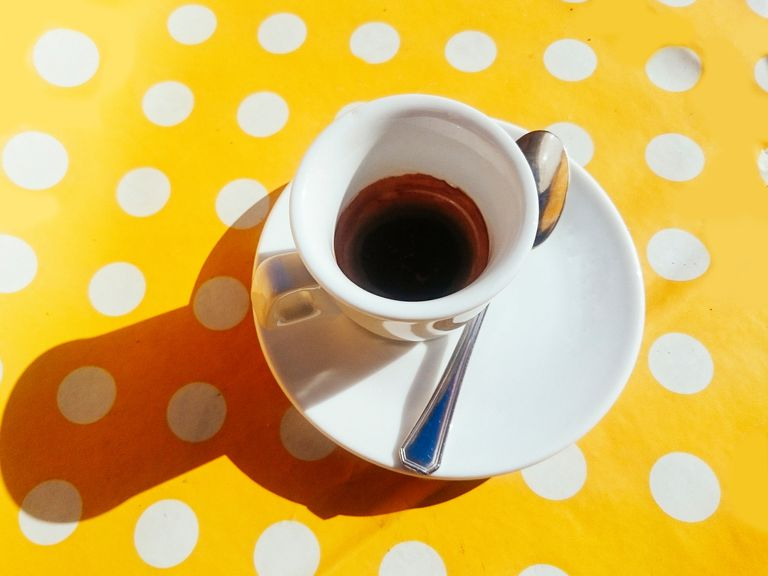 Shot of espresso on yellow tablecloth