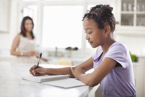Girl doing homework in kitchen.