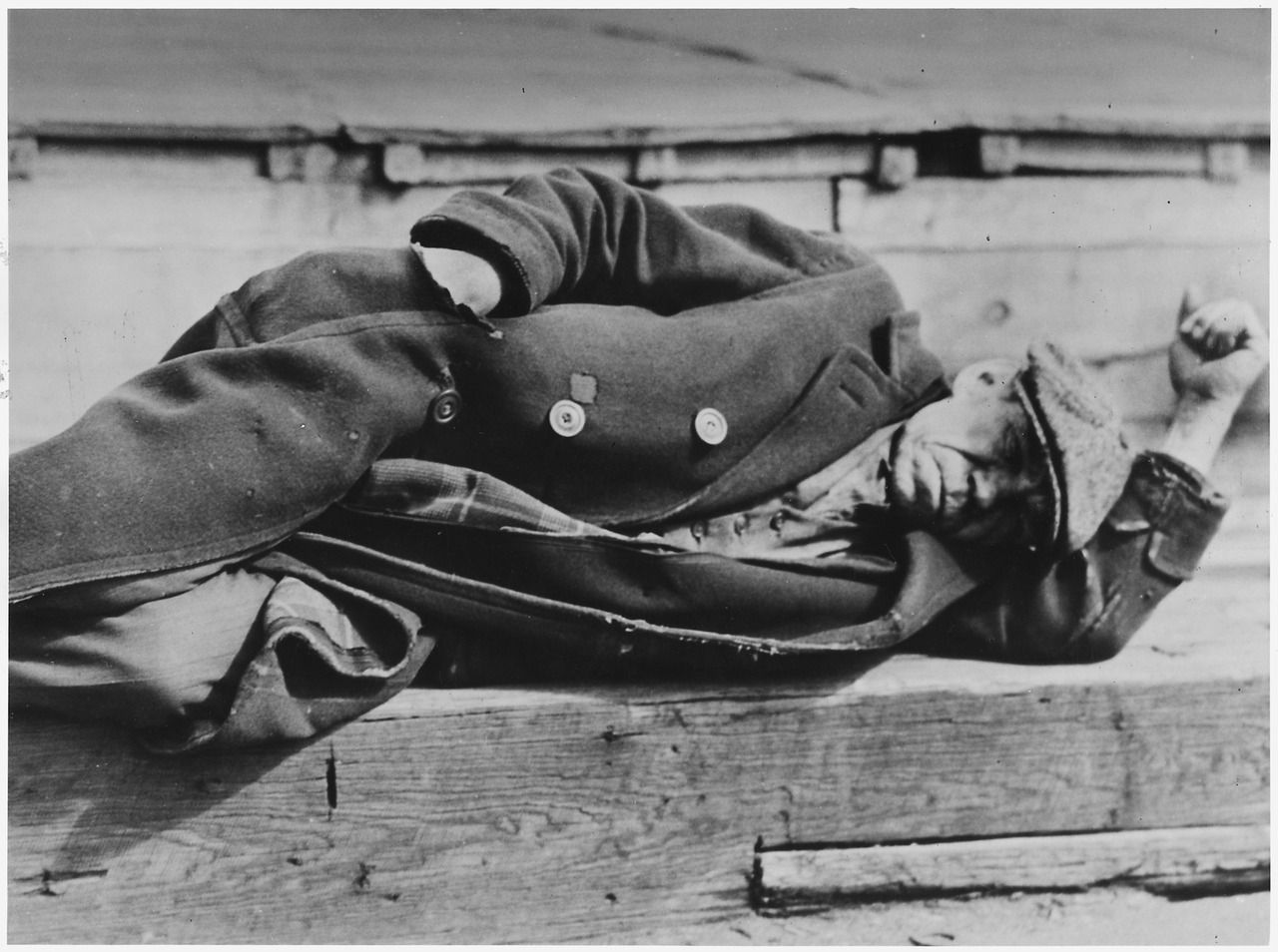 Man laying down at the docks in New York during the Great Depression.
