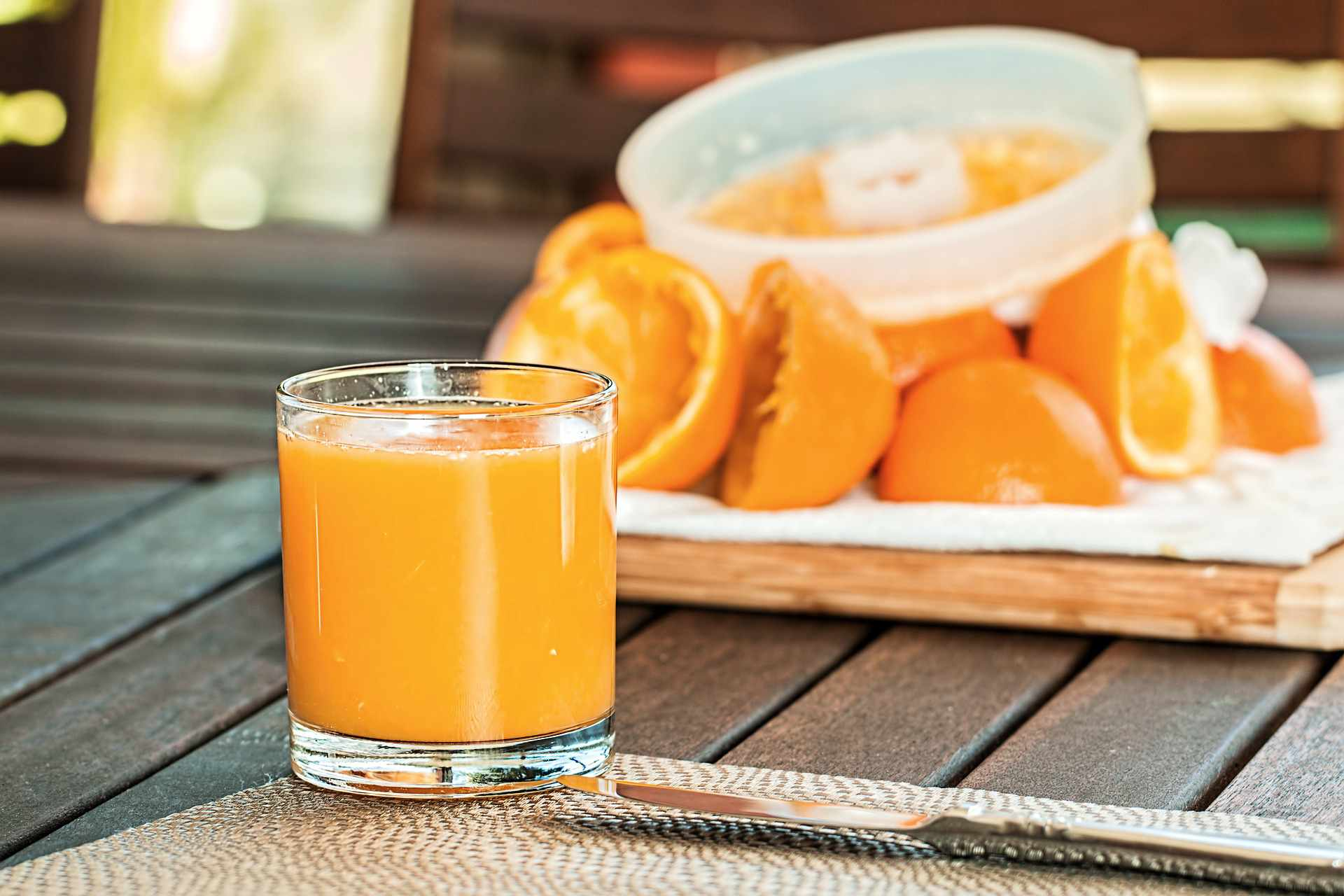Glass of orange juice, oranges, and juicer on a wooden table.