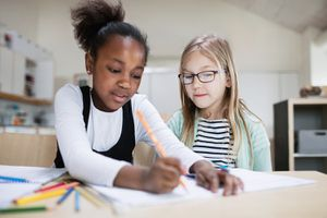 Girl assisting friend while studying in classroom at school