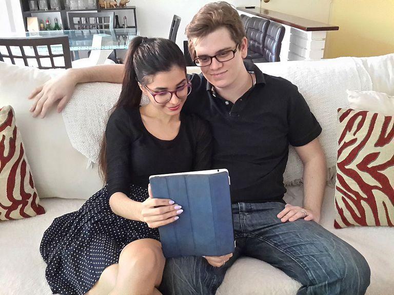 Pareja latina verificando información en una tablet