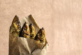 Four smoked herring fish wrapped in brown paper