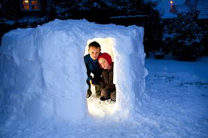 Two young children inside an igloo that they have built in their garden. The Igloo is lit from within.