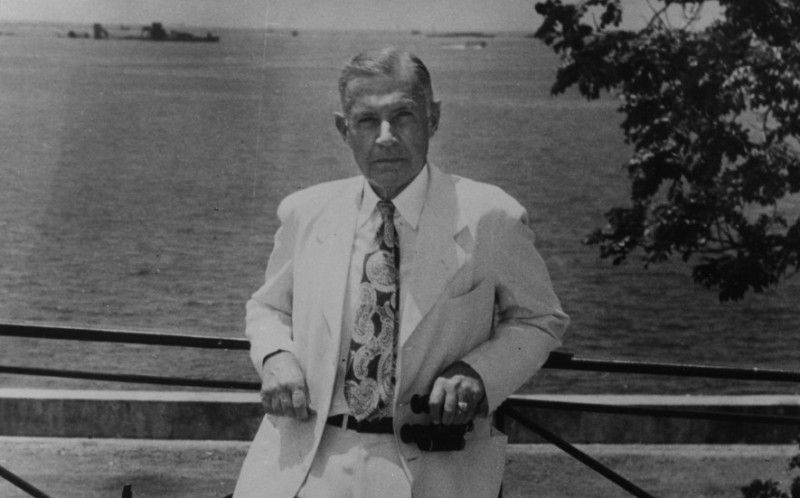 Raymond Spruance wearing a white suit and leaning against a railing in Manila, Philippines.