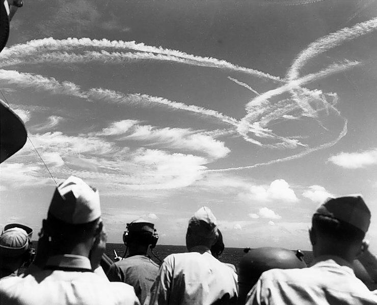 American sailors looking skyward at the contrails formed by aircraft fighting over the fleet.