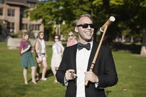 A Smiling White Man Holds a Cigar and Croquet Mallet on the Lawn of a Luxurious Estate