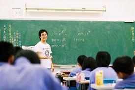 Teacher giving a math lesson to a classroom full of children.