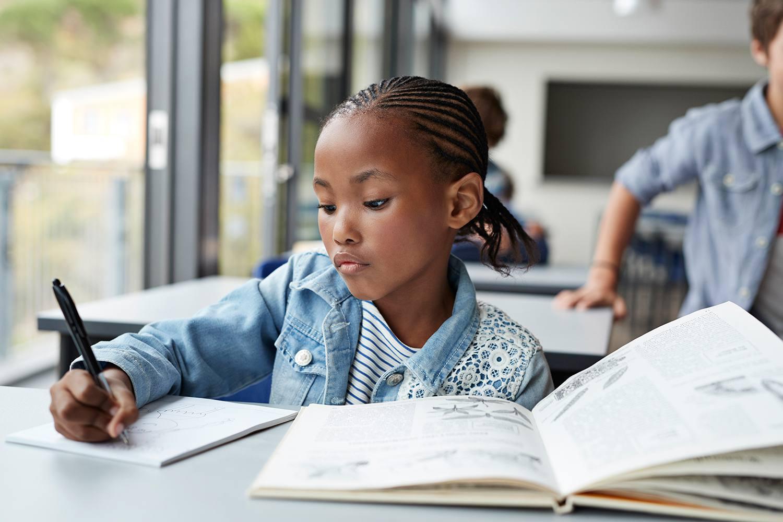 Girl writing in book in classroom