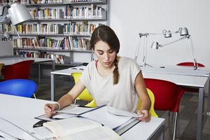 woman studying journals in the library