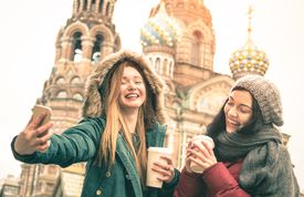 Happy girlfriends taking winter selfie in Saint Petersburg Russia