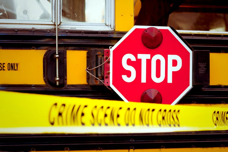A school bus cordoned off with crime scene tape