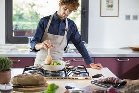 young man preparing broccoli in kitchen