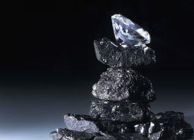 Diamond balanced on top of pile of coal.