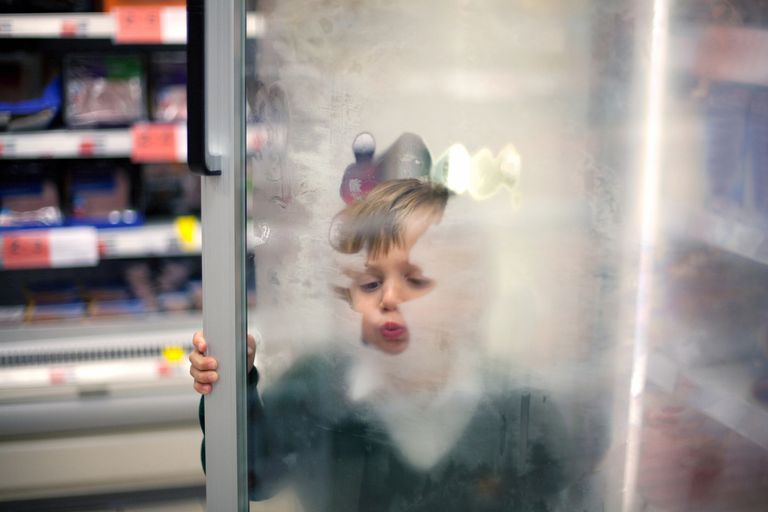 Boy blowing on glass door
