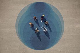 Top view of group of people, sitting in a circle, on painted asphalt