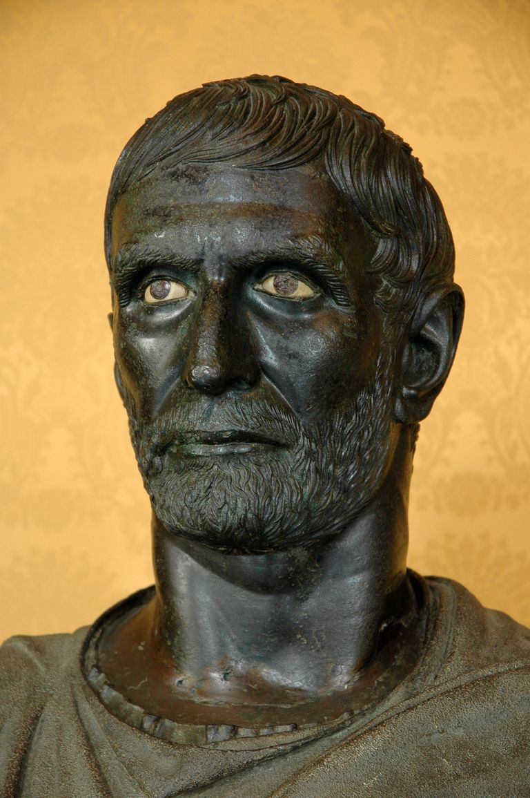 Close up of bust of Lucius Junius Brutus against orange background.