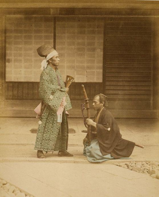 A samurai warrior kneels before his daimyo lord, Japan, 1877