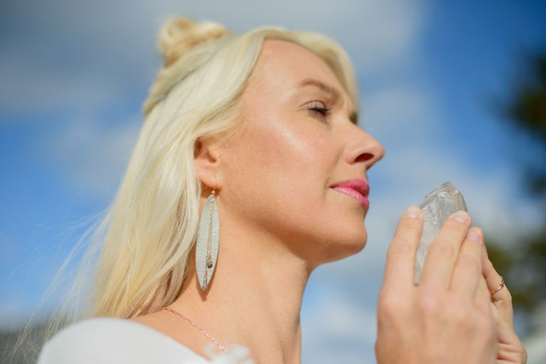 Woman holding crystal with eyes closed.