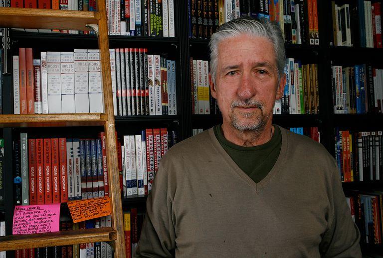 Tom Hayden in front of a bookshelf