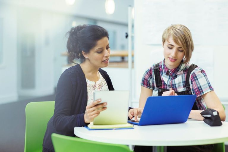 two women working together on a laptop