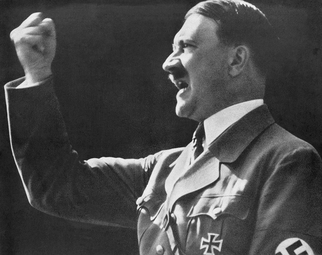 Adolf Hitler holding up a fist while speaking.