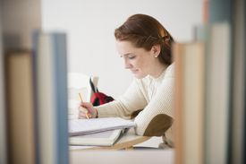 Teenage girl (14-15) studying in library