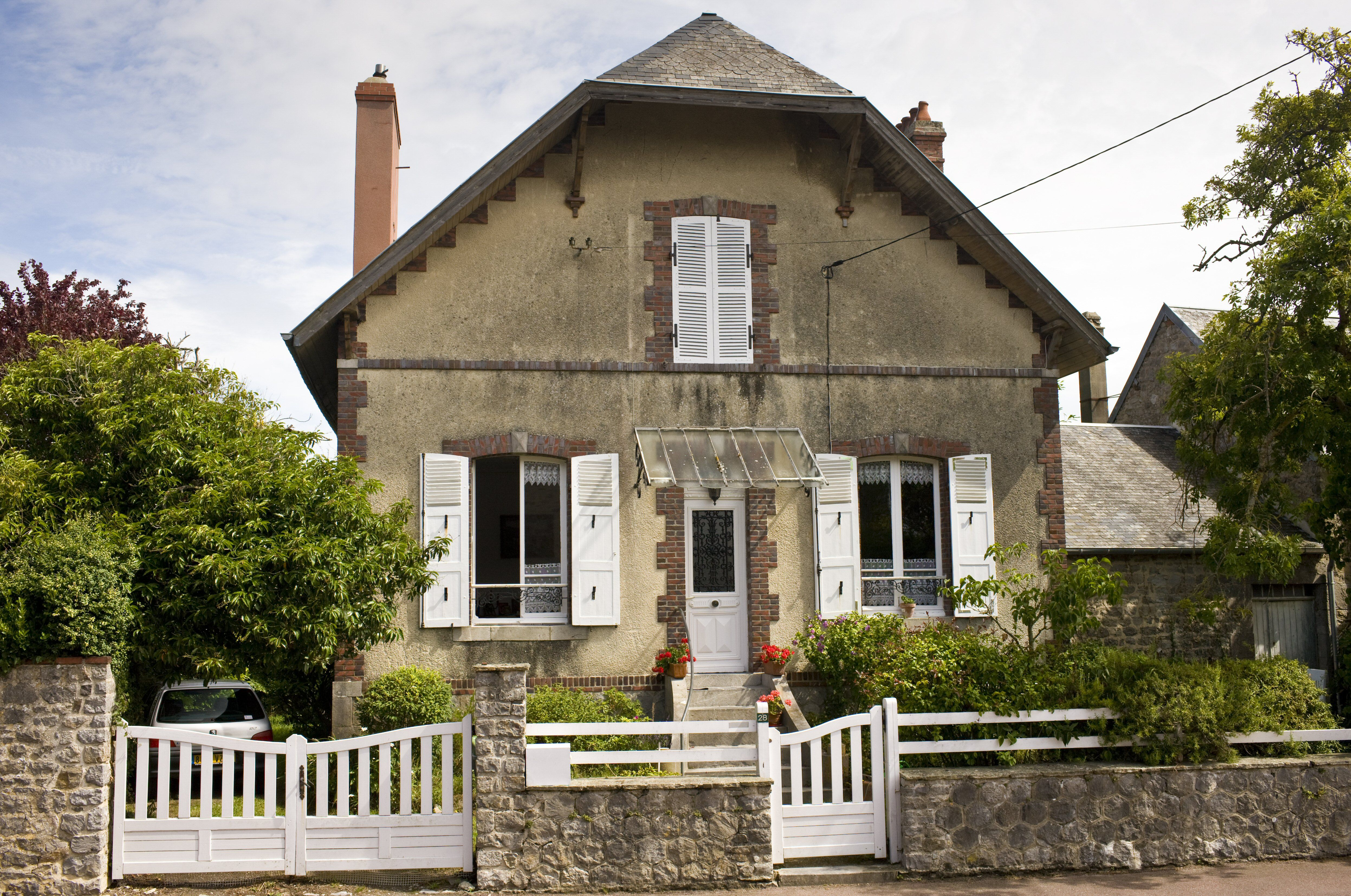 two-story stone house with jerkinhead roof, center door, white shutters, quoin decoration