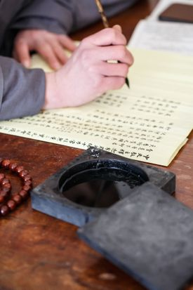 Cropped Hand Of Person Writing On Paper At Table