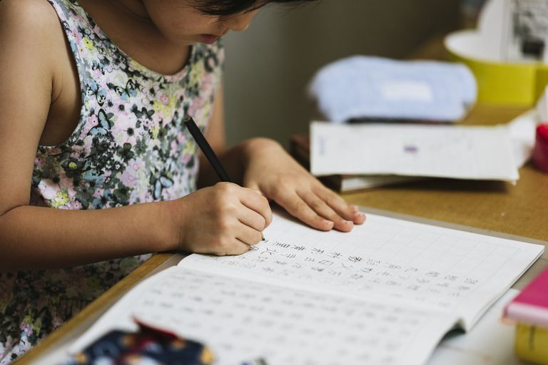 Japanese school girl doing kanji practice at home