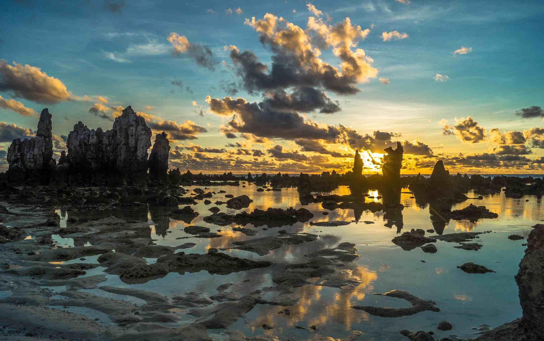 The Sun rises among the rock pinnacles on Anabare beach, Nauru island, South Pacific.