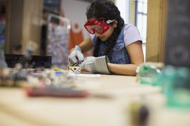 Girl wearing goggles assembling electronics at science center