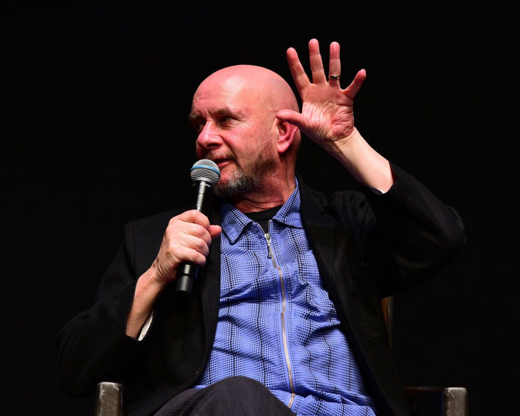 Nick Hornby sitting and speaking into microphone while gesturing