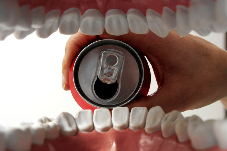 A can of soda poured into a mouth full of white teeth