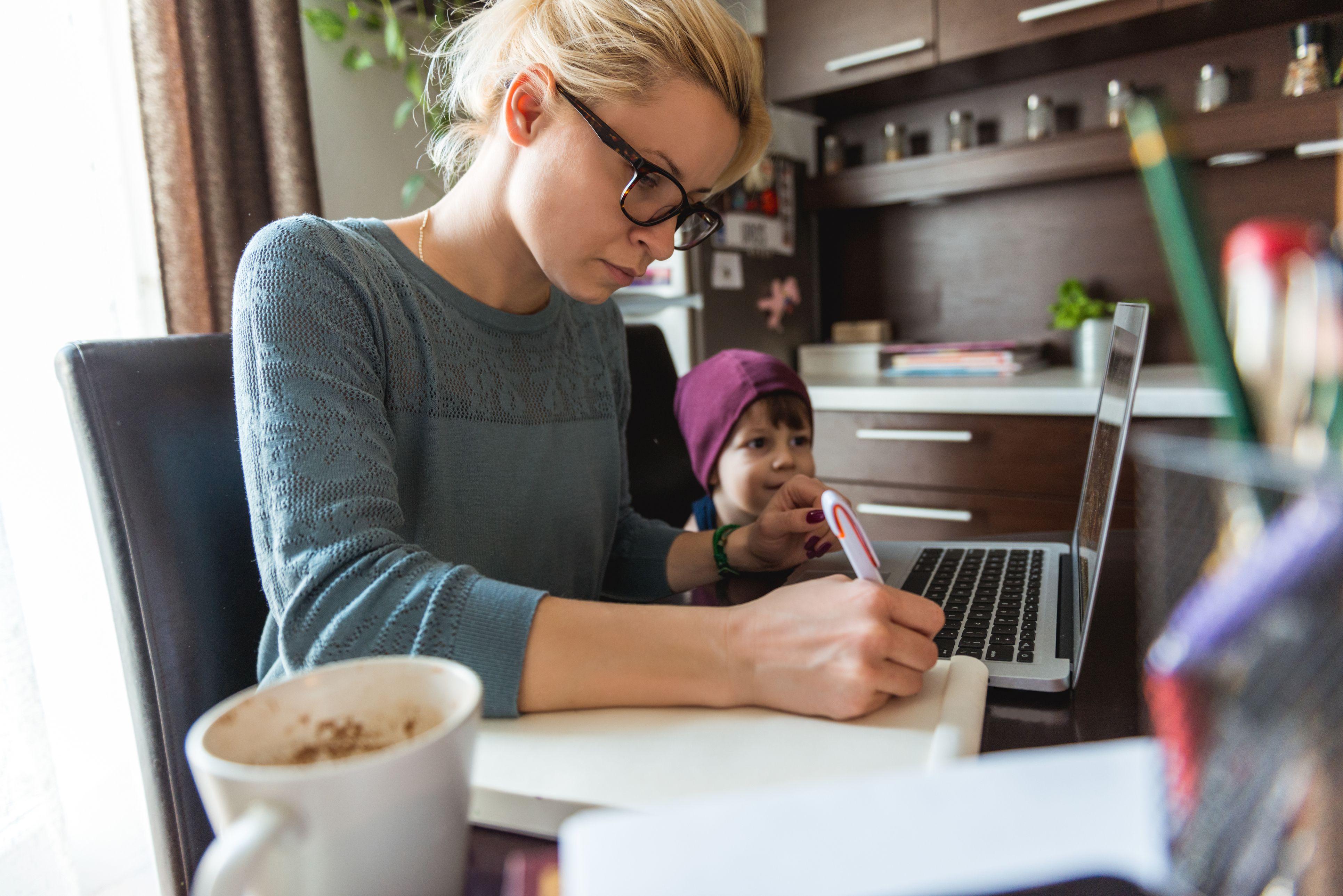 người phụ nữ làm việc với máy tính xách tay với một đứa trẻ bên cạnh cô ấy